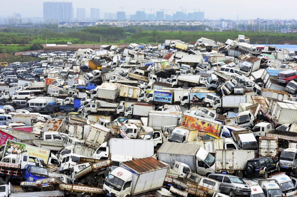 Scrapped high-emission vehicles are seen piled up at a dump site of a recycling centre, waiting to be dismantled, in Yiwu