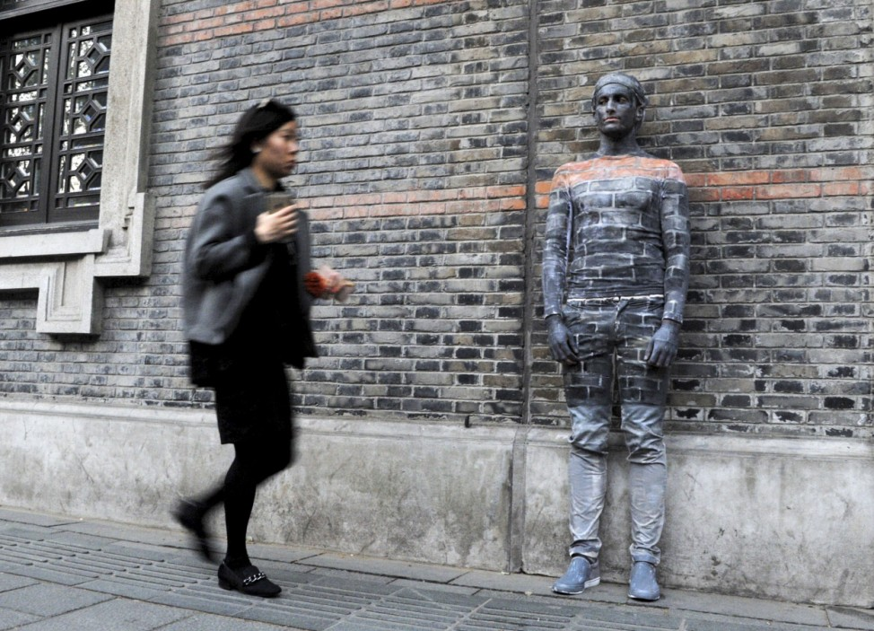 A woman walks past a man blending himself into the background by covering his body with paint, in front of the wall of an ancient building in Shanghai