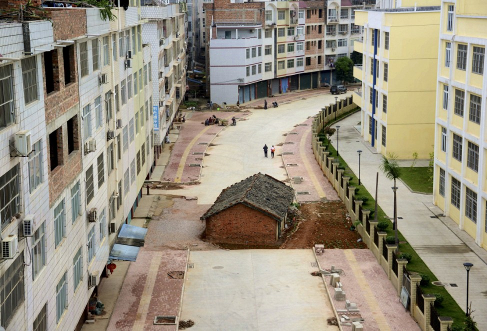 A 'nail house', the last building in the area, sits in the middle of a road under construction in Nanning