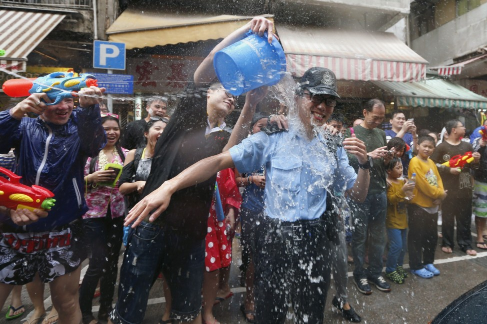 Water is thrown on a police at a water fight during Songkran Festival celebrations at Kowloon City district is known as Little Thailand as there is large number of restaurants and shops run by Thais