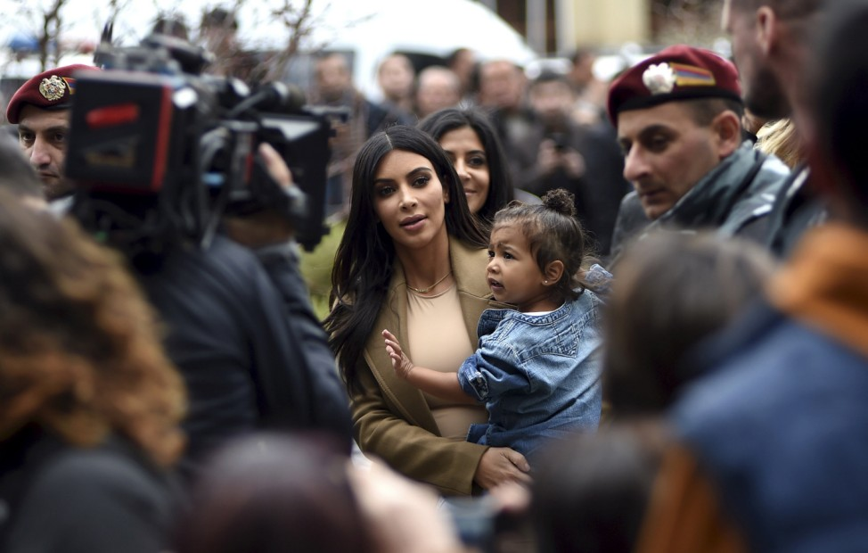 U.S. television personality Kim Kardashian (C) with her daughter North West in hand walks during their visit to Yot Verk Church in Gyumri