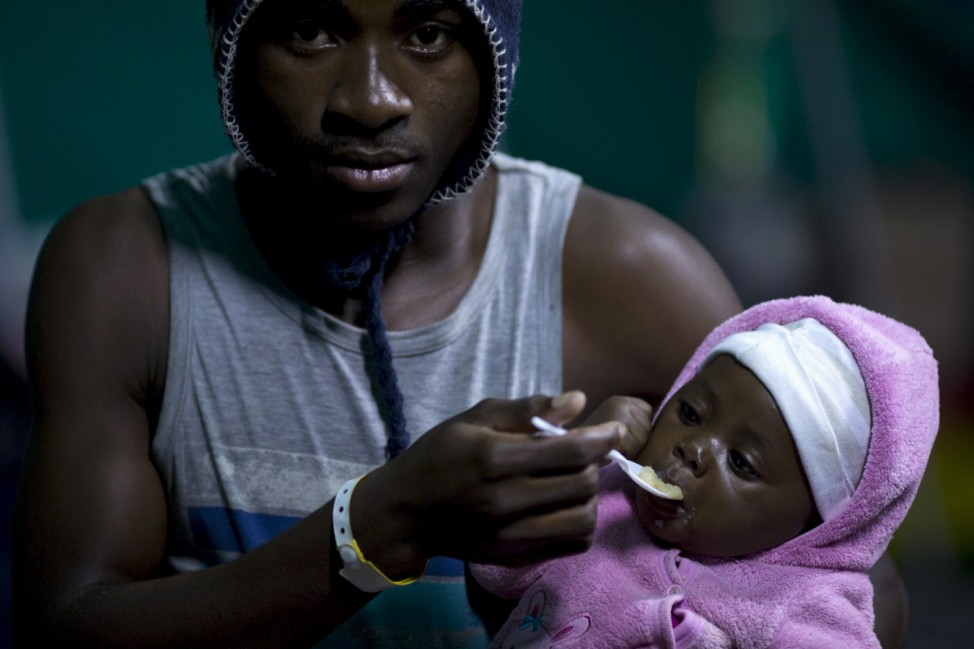 A foreign man feeds his young child in Isipingo