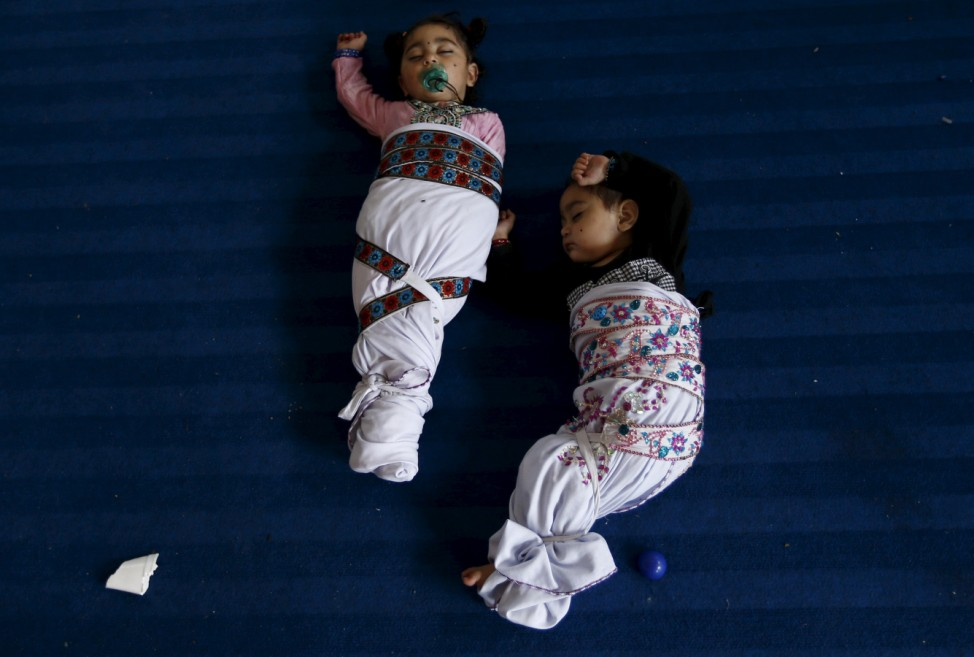 Sikh twins sleep during the Baisakhi festival at Panja Sahib shrine in Hassan Abdel