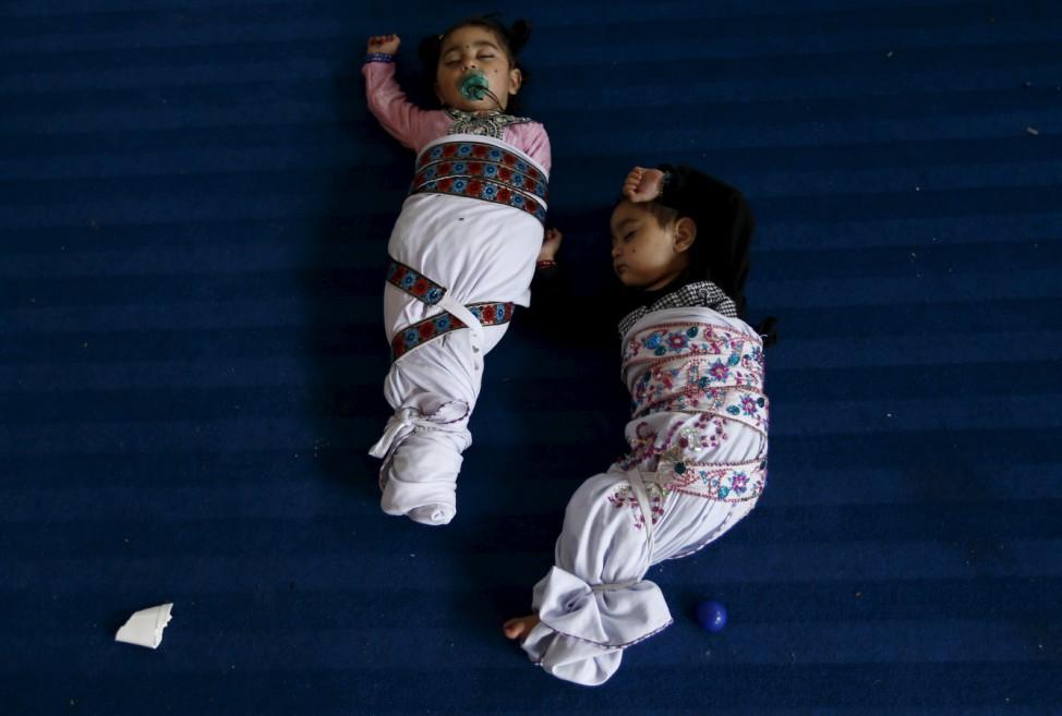 Sikh twins sleep during the Baisakhi festival at Panja Sahib shrine in Hassan Abdel