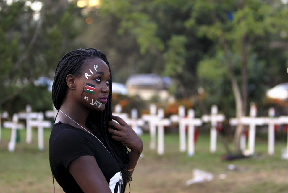 Student wearing facepaint walks past wooden crosses in memory of the Garissa university students who were killed by gunmen, at a memorial concert at the 'Freedom Corner' in Kenya's capital Nairobi