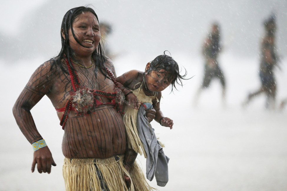 Brazilian Indians from various indigenous ethnic groups dance and sing in the rain during a National Indigenous Mobilization at the Esplanade of Ministries in Brasilia