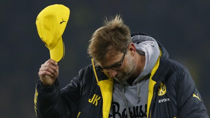 Borussia Dortmund's coach Klopp takes off his cap following his team's German first division Bundesliga soccer match against VFL Wolfsburg in Dortmund