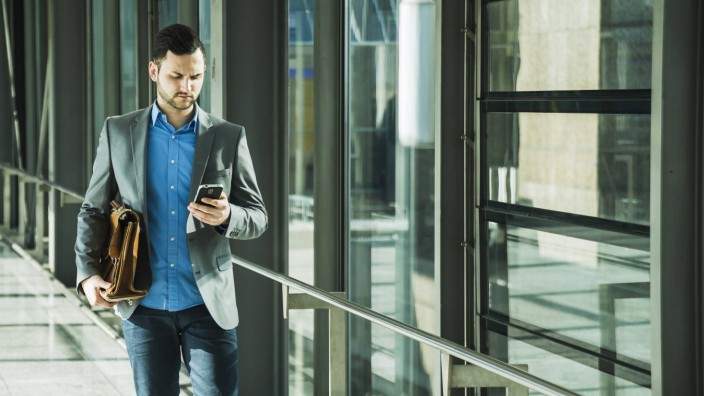 Young businessman walking looking on cell phone model released Symbolfoto PUBLICATIONxINxGERxSUIxAUT