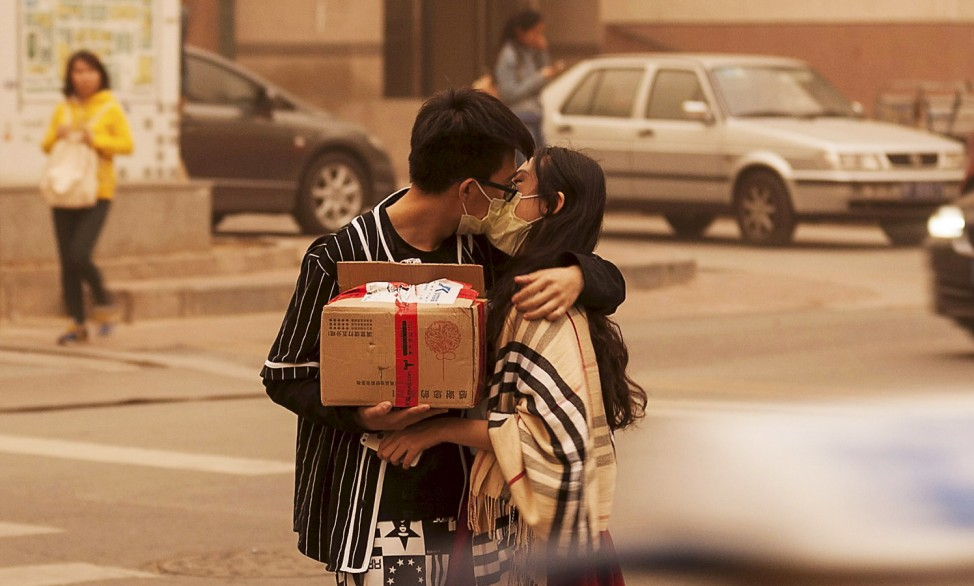 A couple wearing masks kiss along a street during a sandstorm in Beijing