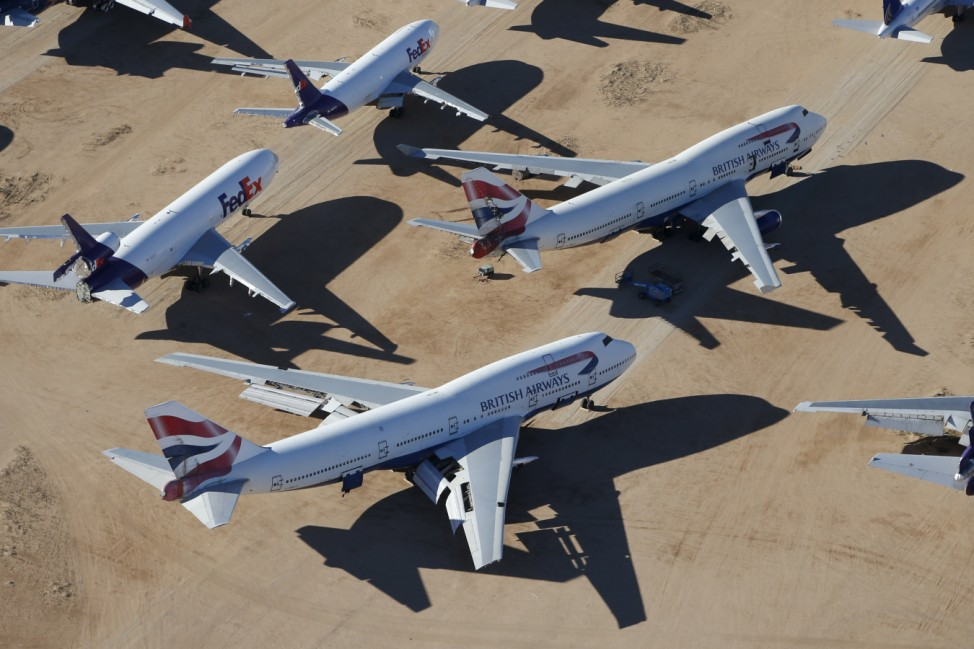 Old airplanes, including British Airways Boeing 747-400s and FedEx planes, are stored in the desert in Victorville