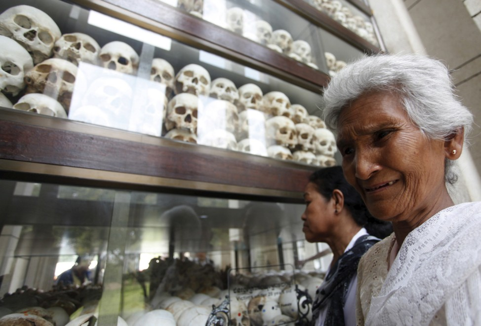 A woman cries in front of the skulls and bones of victims of the Khmer Rouge regime during a Buddhist ceremony at Choeung Ek, a 'Killing Fields' site located on the outskirts of Phnom Penh