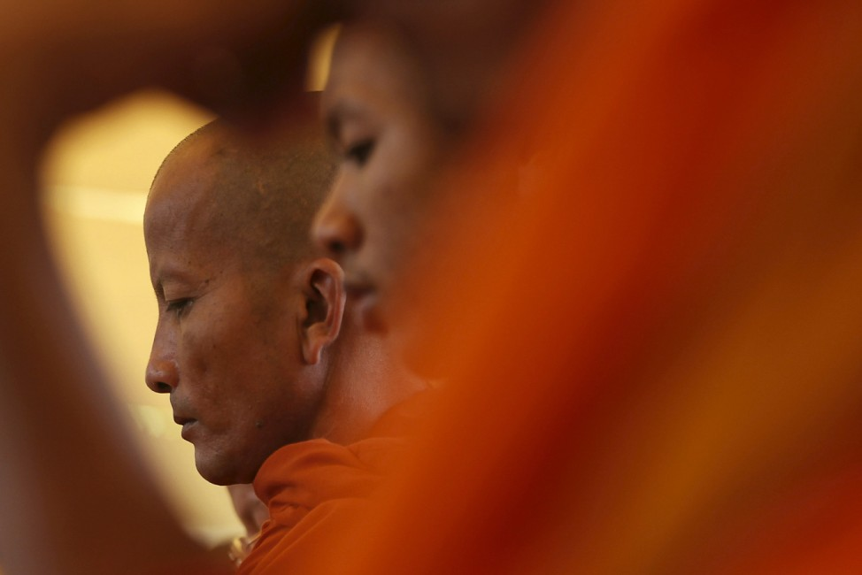 Buddhist monks attend a Buddhist ceremony at Choeung Ek, a 'Killing Fields' site located on the outskirts of Phnom Penh