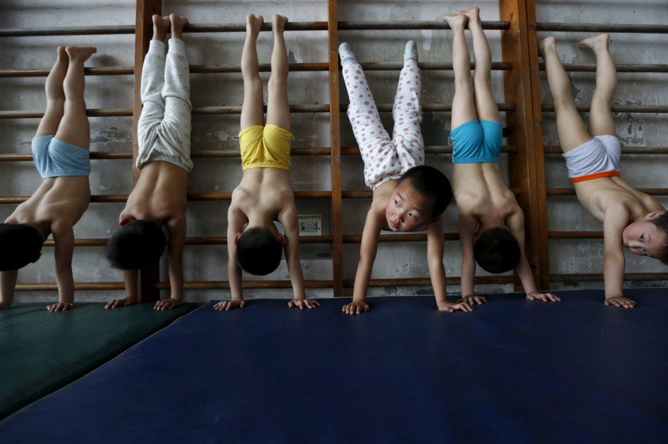 Young gymnasts practice at a gymnasium of a sports school in Jiaxing