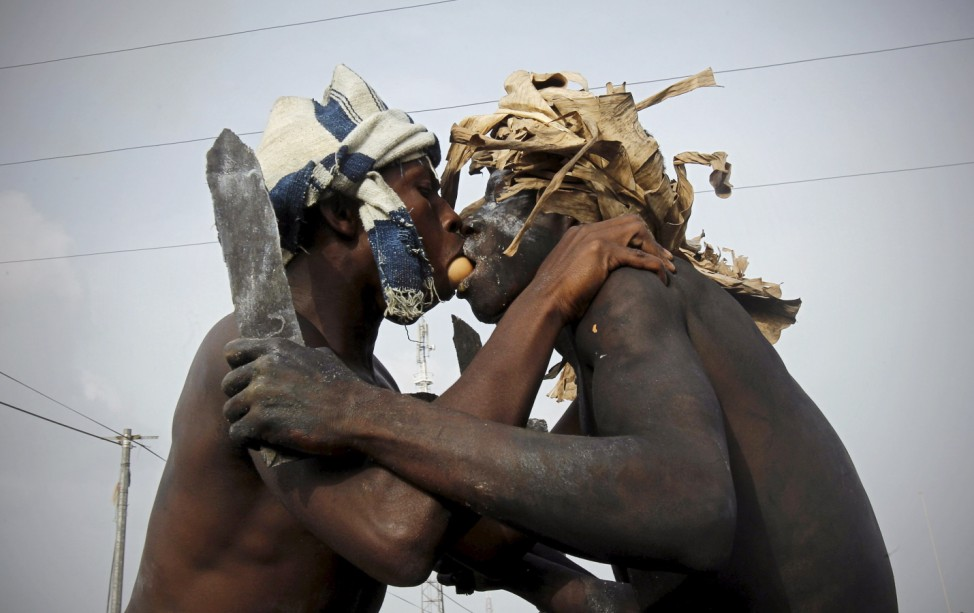 Participants pass an egg using their mouths during a religious ritual as they play the role of traditional fighters in a parade during the Popo (Mask) Carnival of Bonoua