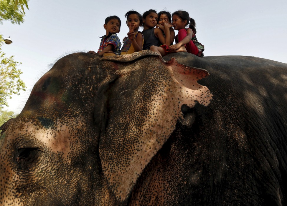 Children gesture as they ride on an elephant outside a temple in the western Indian city of Ahmedabad