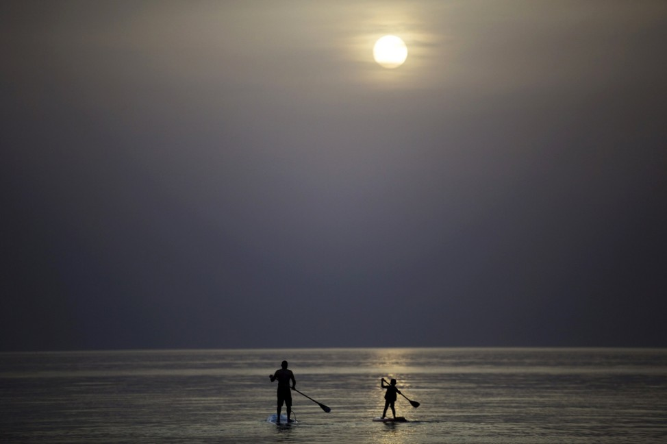Israeli Erez Cohen teaches his six year-old son Itai stand up paddling in the Mediterranean Sea in the coastal city of Ashkelon