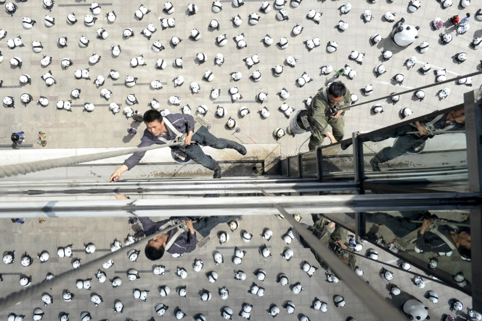 Workers clean windows of an office building above panda installations on display, in Taiyuan