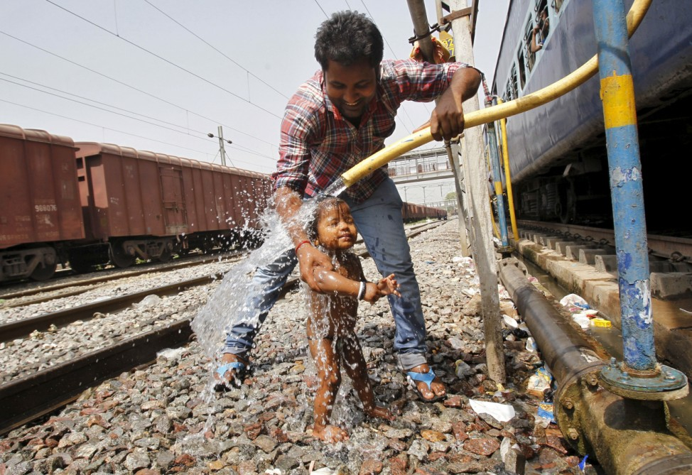 A passenger bathes an child using a pipe that supplies water to trains at a railway station on a hot summer day in Allahabad