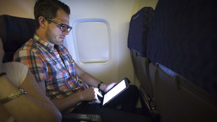 A passenger uses a wireless tablet on an American Airlines airplane, which is equipped with Gogo Inflight Internet service, enroute from Miami to New York