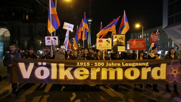 Armenians hold a banner reading 'Genocide' during memorial march after Ecumenical service at cathedral in Berlin