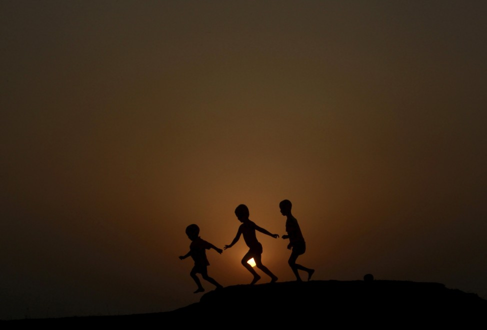 Children are silhouetted against the setting sun as they play on a ground on the outskirts of Agartala