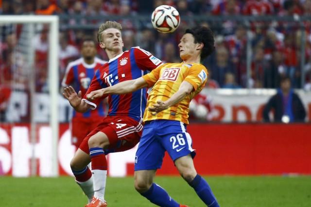 Bayern Munich's Kurt challenges Hertha Berlin's Schulz during Bundesliga first division soccer match in Munich