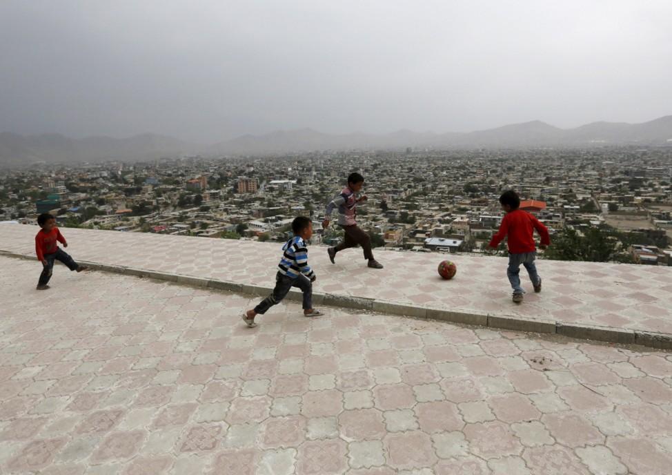 Afghan boys play soccer on a hilltop overlooking Kabul