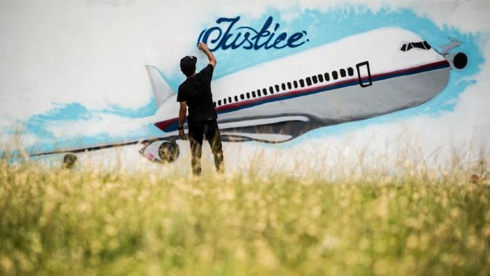 Abschuss von Flug MH17: Mahnung an 298 tote Passagiere: Ein Künstler arbeitet in Kuala Lumpur an einem Graffito zur Erinnerung.