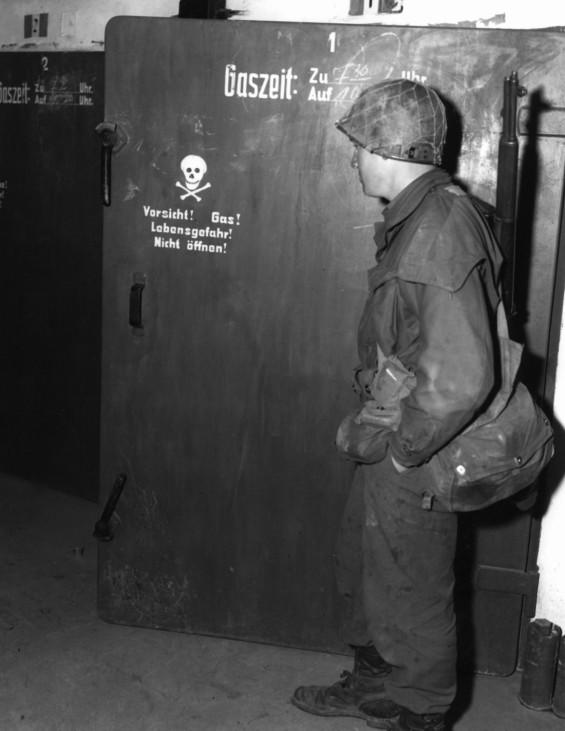 Amerikanischer Soldat examiniert eine Gaskammer in Dachau, 1945