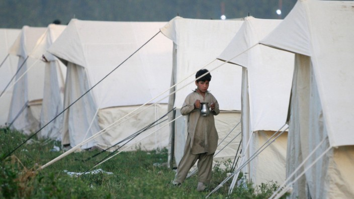 Internally displaced boy, escaping military offensive in Swat valley, stands outside his family tent at UNHCR camp in Mardan district