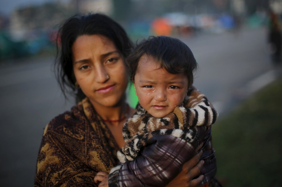 A woman carries her son as she stands outside her makeshift shelter, after Saturday's earthquake, in Kathmandu