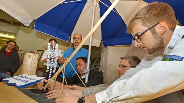 Eichenau: An einem Modell erklärt Bastian Vollert (rechts), wie der Maibaum in die Senkrechte kommt. Ibrahim El-Mahgary (im blauen Pullover) übersetzt.