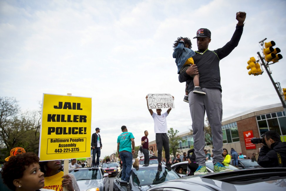 Demonstrators stand on top of vehicles at the intersection of North Avenue and Pennsylvania Avenue in Baltimore, Maryland