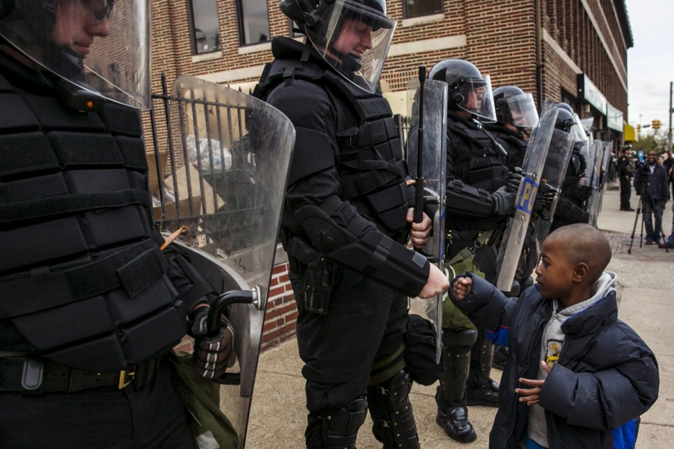 A young boy greets police officers in riot gear during a march in Baltimore, Maryland