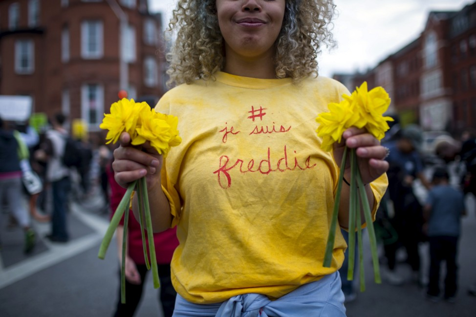 Demonstrator wearing a T-shirt on which the words, 'I am Freddie' are written, holds flowers at North Avenue and Pennsylvania Avenue in Baltimore, Maryland