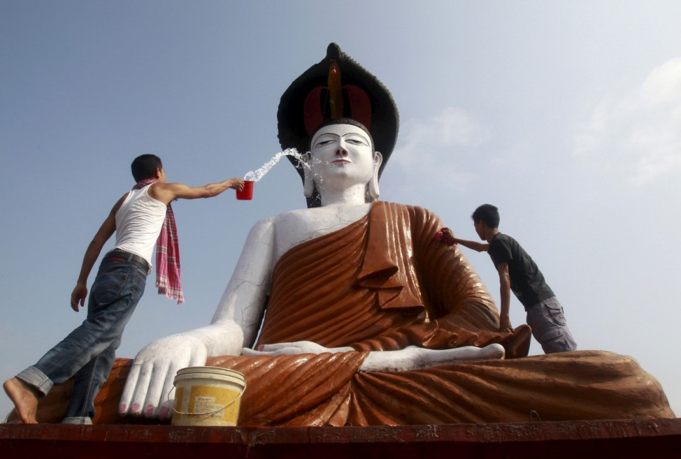 Men clean a statue of Lord Buddha in a temple on the eve of the Buddha Purnima festival, also known as Vesak Day, in Agartala