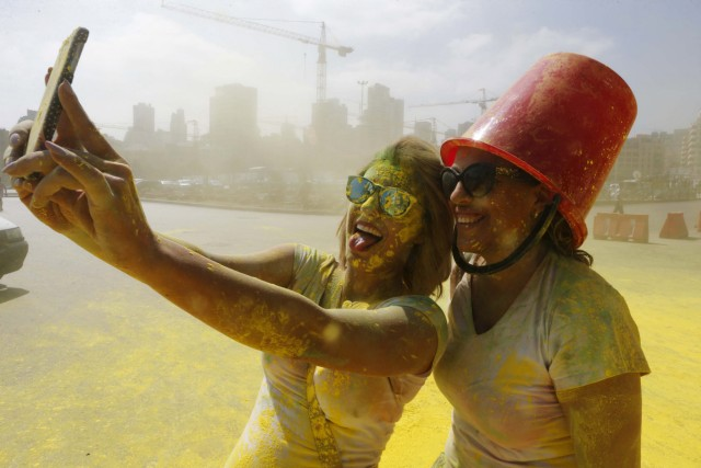 People take a selfie while covered in colour powder during the first color run called 'Alwan LB' in Beirut