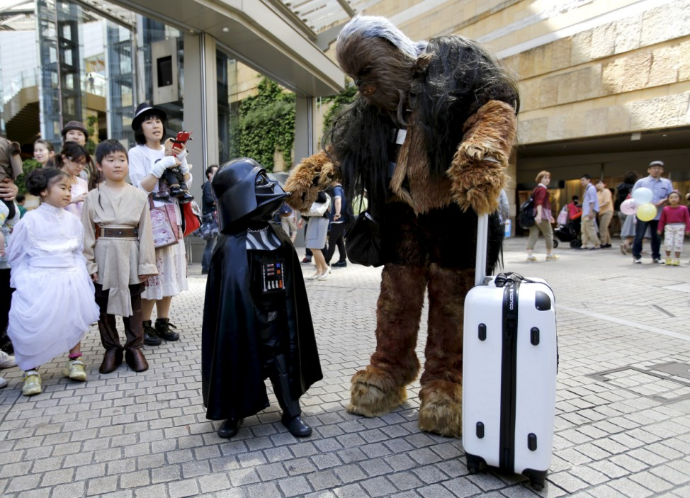 Cosplayers dressed as 'Star Wars' characters Chewbacca and Darth Vader talk at a Star Wars Day fan event in Tokyo