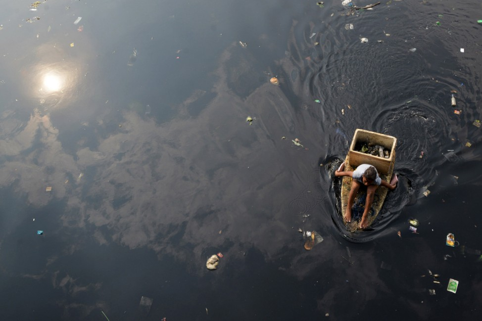 Woman paddles in a makeshift boat as she collects recyclable trash from a polluted river in Navotas city
