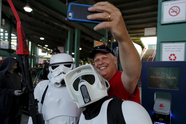 A baseball fan poses for a selfie with people dressed as Star Wars storm trooper characters from the 501st New England Garrison before the MLB baseball game between the Tampa Bay Rays and the Boston Red Sox at Fenway Park in Boston