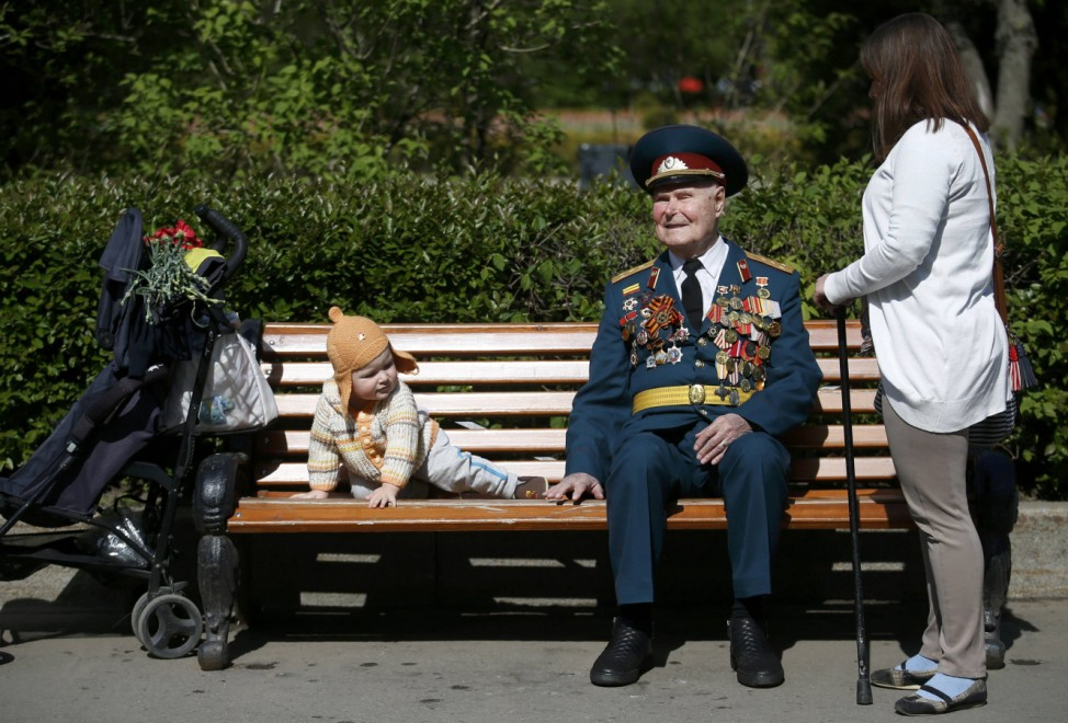 Blind World War Two veteran sits on bench next to child during Victory Day celebrations at Gorky park in Moscow