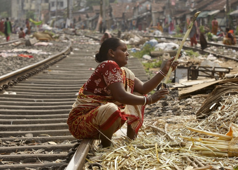 A woman peels sugarcanes on a railway track to sell it to sugarcane juice vendors at a slum area in Kolkata