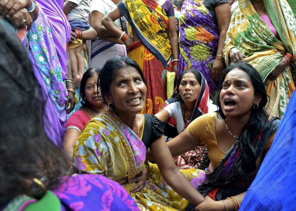 Women mourn the death of their relative who died after a wall collapsed in an earthquake, in Bihar