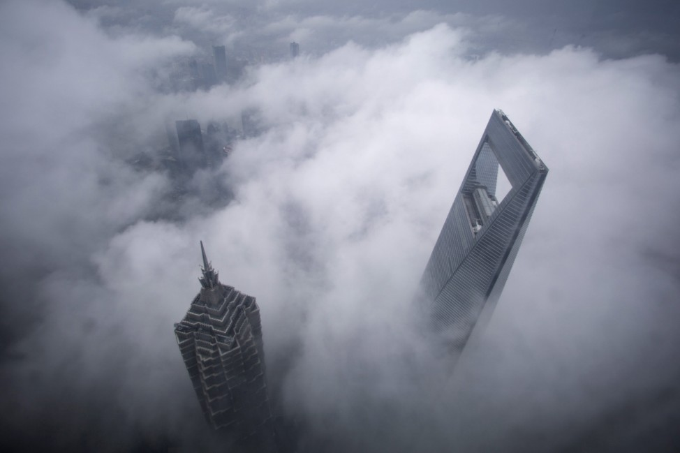 Skyscrapers Shanghai World Financial Center and Jin Mao Tower are seen during heavy rain at the financial district of Pudong in Shanghai