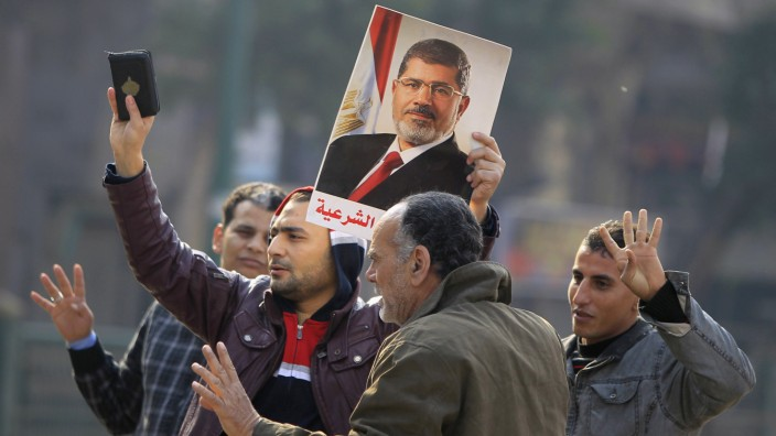 Supporters of the Muslim Brotherhood and ousted Egyptian President Mohamed Mursi hold a copy of the Koran and Mursi's picture at Talaat Harb Square, in Cairo