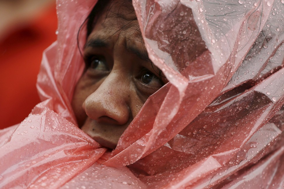 A women wearing a rain poncho looks on during a demonstration demanding Guatemalan President Otto Perez Molina's resignation, in Guatemala City