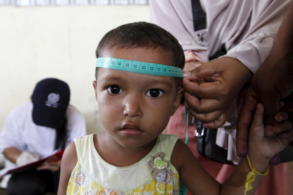 A Rohingya child, who recently arrived in Indonesia by boat, is measured and weighed at a shelter in Kuala Langsa
