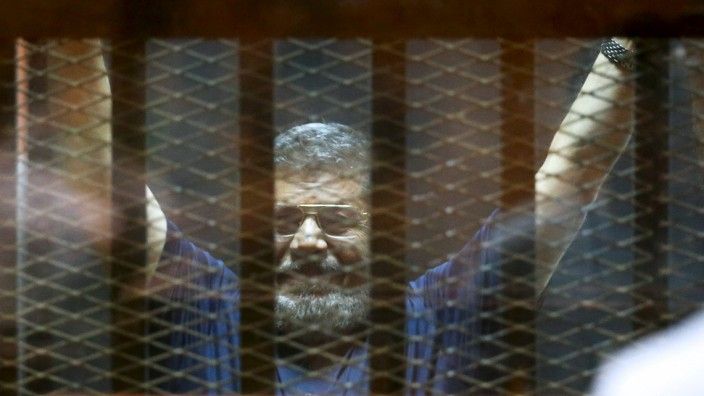 Former Egyptian President Mursi waves during his trial at a court in the outskirts of Cairo