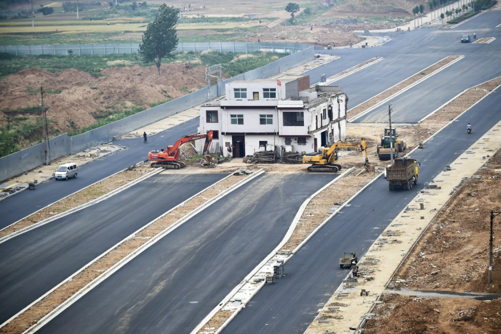 A three-storey nail house, the last building in the area, with a Chinese national flag on its rooftop is seen in the middle of a newly-built road in Luoyang