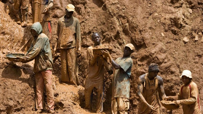 Gold miners form a human chain while digging an open pit in north-eastern Congo